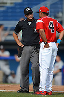 Umpire Joe George explains a call to Batavia Muckdogs manager Angel Espada (4) during a game against the Tri-City ValleyCats on July 14, 2013 at Dwyer Stadium in Batavia, New York.  Tri-City defeated Batavia 7-0.  (Mike Janes/Four Seam Images)