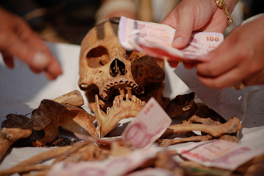 Banknotes are placed on unclaimed human remains taken out of graves during a Thai Chinese ceremony at the Mang Teung Sua Jung Cemetery in Chonburi province southeast of Bangkok March 18, 2012. Every 10 years, hundreds of people wearing white, a customary colour for funerals and visiting temples, gather at this cemetery to exhume and cremate corpses as they believe they are helping the dead who have no friends or relatives. The ashes of the unclaimed bodies are spread on the sea to make room at the burial ground for more unclaimed bodies in the coming years. The tradition originated 90 years ago after diseases like Malaria killed many Thais of Chinese descent living in Chonburi.  REUTERS/Damir Sagolj (THAILAND)