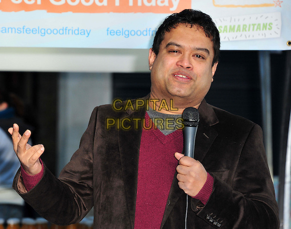 Paul Sinha photocall to launch Samaritan's Feel Good Friday. British stand-up helps to launch Samaritan's fundraising day Feel Good Friday (February 1), where employees are encouraged to organise light-hearted activities for a good cause. Market Place, Spitalfields Market, London, United Kingdom, 17th January 2013..half length holding brown red jacket jumper microphone speaking hand .CAP/BF.©Bob Fidgeon/Capital Pictures.