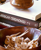 A collection of bleached bones in a wooden bowl beside a pile of books on Africa