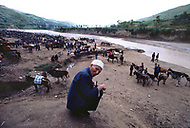 September, 1985. Shaanxi Province, China. Trading ponies at the market in Zhidan. This small town was called Bao'an when the Red Army settled here in 1936. Men privately negotiate the sale of their animals in a traditional way, using sign language covered with a cloth.