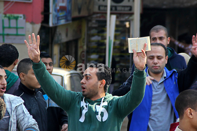 A small group of Egyptians hold up copies of the Koran and make the four fingered gesture associated with the clearing of a Muslim Brotherhood demonstration in the Rabaa Square which followed the ouster of Mohammed Morsi from the Presidency 03 July 2013, during a protest on al-Haram Street, Cairo, Egypt, 28 November 2014. According to unconfirmed reports at least two Egyptian army officers have been killed and soldiers injured in seperate incidents in Egypt, as some hardline Salafi Muslims heeded calls to hold protests against what they see as the secularisation of Egyptian society and the proliferation of indecent activities, to which Egyptian authorities responded by tightening security measures throughout the country and it has been alleged killing an as yet unconfirmed number of protesters. Photo by Amr Sayed