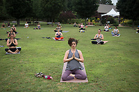 Karen Pollock of Fayetteville meditates, Saturday, June 20, 2020 at the Botanical Gardens of the Ozark in Fayetteville. Fayetteville Yoga Fest hosted a yoga class with about 60 people on the lawn of the garden to celebrate the summer solstice, the first day of summer and longest day of the year. Check out nwaonline.com/200621Daily/ for today's photo gallery. <br /> (NWA Democrat-Gazette/Charlie Kaijo)