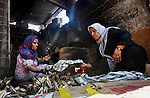 Palestinian women bake bread on the rubble of their house which witnesses said was destroyed during the Israeli offensive in Shejaiya neighborhood after a ceasefire was declared, in Gaza city on August 30, 2014.  An open-ended ceasefire, mediated by Egypt, took effect on Tuesday evening. It called for an indefinite halt to hostilities, the immediate opening of Gaza's blockaded crossings with Israel and Egypt, and a widening of the territory's fishing zone in the Mediterranean. Israel launched an offensive on July 8, with the declared aim of ending rocket fire into its territory. Photo by Mohammed Talatene