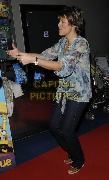 KATE SILVERTON .Attending the film premiere of 'Bob the Builder: The Legend of the Golden Hammer' at Vue West End cinema, Leicester Square, London, England, May 15th 2010. .arrivals full length jeans blue green  print top blouse peep toe tan brown shoes side hands arms funny profile .CAP/CAN.©Can Nguyen/Capital Pictures.