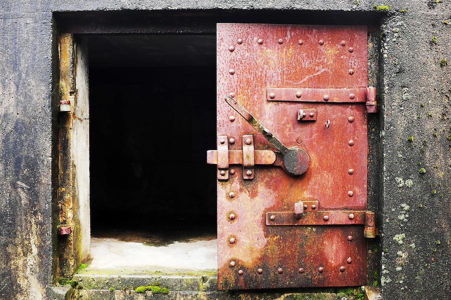 Open rusty red steel door in concrete bunker window, Artillery Hill, Fort Worden State Park, Port Townsend, Washington, USA