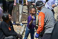 April 26, 2013  (Baltimore, Maryland)  San Francisco Mayor Edwin M. Lee (r) high-fives a young girl while planting flowers at the Baltimore park with Mayor Stephanie Rawlings-Blake (l). Mayor Lee visited Baltimore for a day of community service after his city lost a friendly Super Bowl bet when the Ravens beat the 49ers. (Photo by Don Baxter/Media Images International)