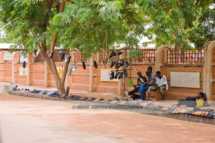 Young men line the streets and trees with shoes for sale in Ouagadougou, Burkina Faso.