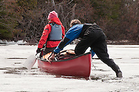 Canoeists propel their canoe over a frozen lake during an early spring trip to Lady Evelyn-Smoothwater Provincial Park in Ontario Canada.