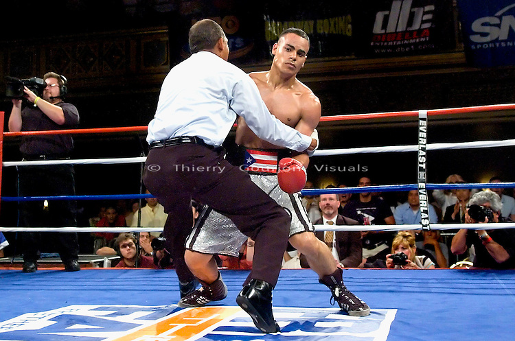 Manhattan Center, N.Y: (l-r) Edgar Santana  is held  by the referee while he struggles to get back  up, after being knocked out by  Harrison Cuello during their 10 rounds Junior Welterweight fight, Wednesday, June 20, 2007.  Cuello won the upset victory over heavily favorite Santana by KO in the 3rd round..