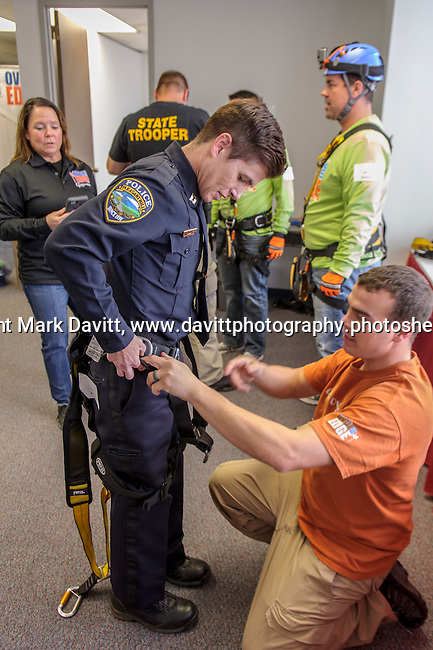 """Captain Amy Kramer from the Pleasant Hill Police Department gets fitted for a harness for her """"Over the Edge"""" volunteerism. She and other volunteers rappelled down the side of the 345-ft. Financial Center in Des Moines for Special Olympics Iowa Oct. 26."""