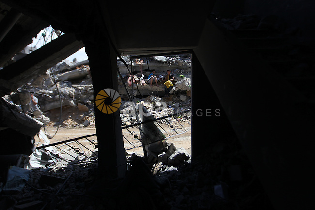 Palestinians gather around the the remains of their house that witnesses said were destroyed in an Israeli offensive, after a ceasefire was declared in the Shejaia neighbourhood, east of Gaza City. September 6, 2014. Calm returned to the coastal enclave in a August 26 ceasefire, and Gazans were gradually starting to rebuild their lives after a bloody and destructive 50-day war, the deadliest for years. Photo by Ashraf Amra