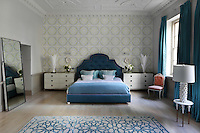 The master bedroom retains the original Georgian architectural details including the original plasterwork on the ceiling, which dates back to the 1750s. The room has soft accent colours and the blue and cream rug is by Martin Lawrence Bullard