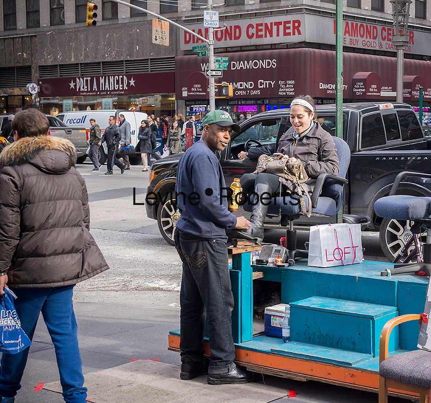 A woman gets her boots shined at a shoe shine stand on Sixth Avenue in New York is seen on Friday, November 15, 2013. (© Richard B. Levine)