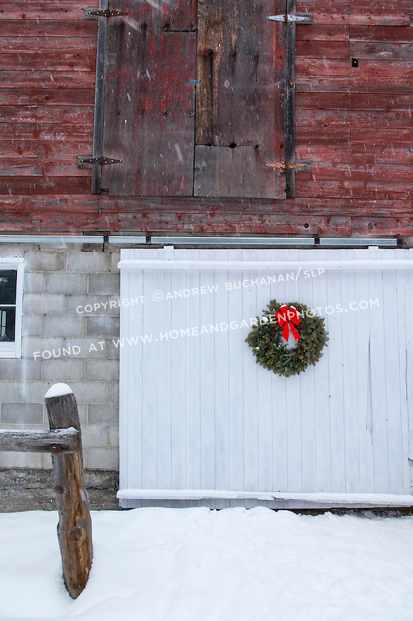 A pine wreath adds a touch of the holidays to a weather-beaten red barn in this winter country scene.