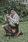 Scottish man dressed in a Kilt kneeling with his sword HDR