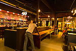 A group of friends playing shuffleboard at the 41st Street Pub and Aircraft Sales, a bar in the Avondale neighborhood in Birmingham, Alabama