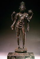 "India: Avalokitesvara, 9th century. Bronze, 28"" high. Kurfinar, Eihar. Here he is ""the four-armed Buddhist Divinity"" standing on a lotus. Lower right hand open in gesture of granting boons; upper holds rosary; lower left grasps stalk of lotus; upper holds a book; third, vertical eye in center of forehead. Headdress in form of Buddha in Meditation."