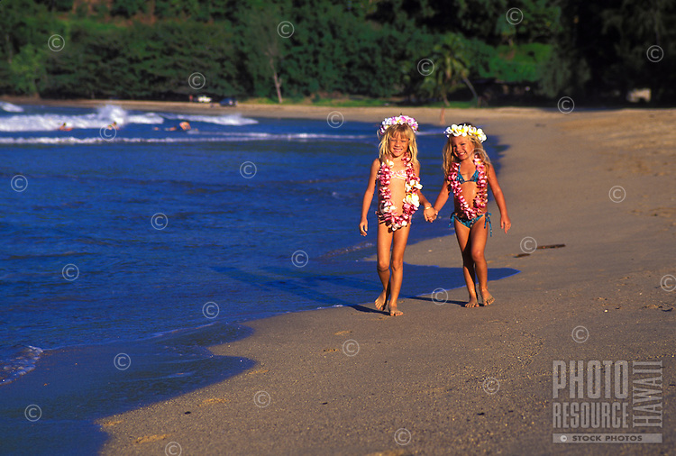 Two young girls holding hands and walking on Kalihiwai beach with flower leis, Kauai