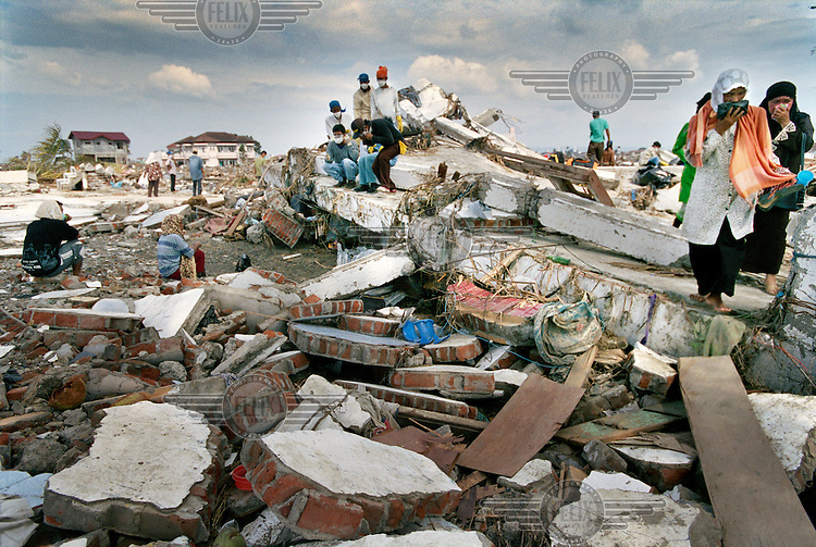 Volunteers and survivors look for bodies in the Ulele district following the tsunami which struck South Asia on 26/12/2004..An underwater earthquake measuring 9 on the Richter scale triggered a series of tidal waves which caused devastation when they struck dry land. 12 countries were affected by the tsunami, with a combined death toll of over 280,000. Aceh, the closest landfall to the epicentre of the quake, suffered the greatest loss of life.