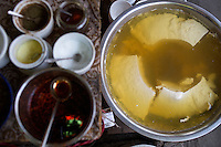 A large pot of soft tofu used in dou hua sits next to spices, sweeteners, and flavoring, at a restaurant off the Shibati staircase in central Yuzhong district, Chongqing, China. Dou hua is a porridge-like dish made of very soft tofu. Shibati is an old neighborhood centered around this staircase. The area is slated for renovation and all businesses and residents must be gone by October 2014.