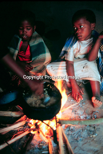 disiaids00368.  Social Issues, Aids: Health. Aids Orphans. Children infected by Aids in their home in Nbeni, Natal South Africa. Nov-99. Sitting around the cooking fire. Three legged black pot. Poverty..©Per-Anders Pettersson/ iAfrika Photos.