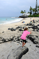 8 year old child leaping on rocks. La'aloa Bay Beach, also known as Disappearing Sands Beach or White Sands Beach. Kona, Big Island, Hawaii