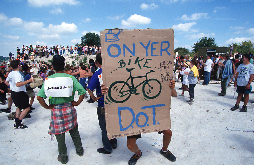 """On yer bike D.O.T"" placard holding protester in Cutting. Road Protest actions at Twyford Down, near the Donga pathways, outside Winchester, against the M3 road extension. 1992-94<br />
