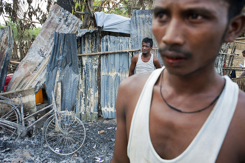 Muslim men survey what is left of their village of Chauk Te after it was destroyed by mobs. Residents hid while attackers from nearby villages burned their homes, one by one, over a period of 3 hours. The attack came after a Muslim woman accidently bumped into a novice Buddhist monk.<br />