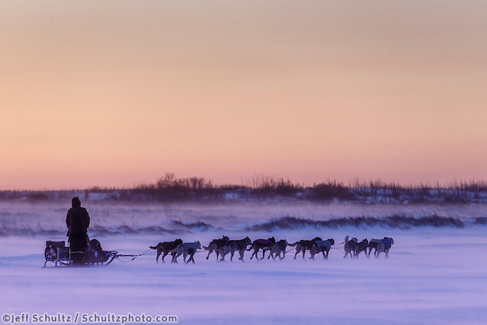Aaron Burmeister runs on the slough in 30 mph wind leaving the Unalakleet checkpoint at sunset on Sunday  March 15, 2015 during Iditarod 2015.  <br /> <br /> (C) Jeff Schultz/SchultzPhoto.com - ALL RIGHTS RESERVED<br />  DUPLICATION  PROHIBITED  WITHOUT  PERMISSION