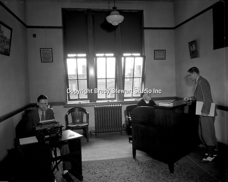 Pittsburgh PA: Student meeting with a College of the Arts professor, Duquesne University and grad student typing a letter - 1932