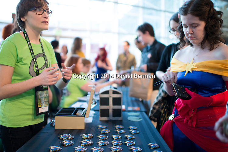 Ari Crossby of Vancouver, B.C., right, pays for some merchandise before entering the Carol Corps Celebration Thursday March 27, 2014 at the Museum of Flight in Seattle. Held the day before Emerald City Comicon kicked off, the event raised funds for Girls Leadership Institute and offered a chance for fans to meet and chat with Captain Marvel writer Kelly Sue DeConnick and Ms. Marvel writer G. Willow Wilson. Photo by Daniel Berman for WIRED.com