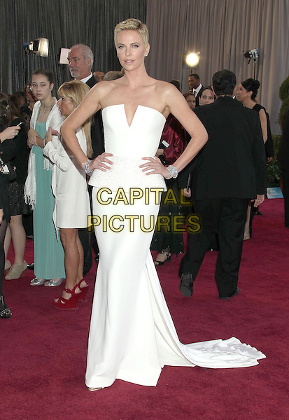Charlize Theron (wearing Dior Couture).85th Annual Academy Awards held at the Dolby Theatre at Hollywood & Highland Center, Hollywood, California, USA..February 24th, 2013.oscars full length dress white strapless peplum short cropped hair pixie cut hands on hips train .CAP/ADM/RE.©Russ Elliot/AdMedia/Capital Pictures.