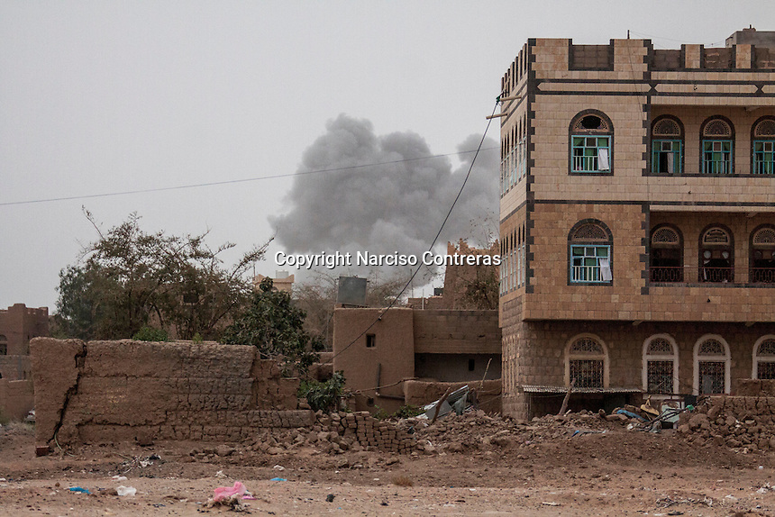 July 15, 2015 - Sa'dah, Yemen: Smoke rises from a house building as a fighter jet from the Saudi-led coalition strikes the northern city of Sa'dah, the stronghold of the Houthi movement in Yemen. One family was buried under the rubble during the attack. Two members: the mother and one son (not pictured) died from their injuries, while another son and one daughter (not pictured) survived. (Photo/Narciso Contreras)