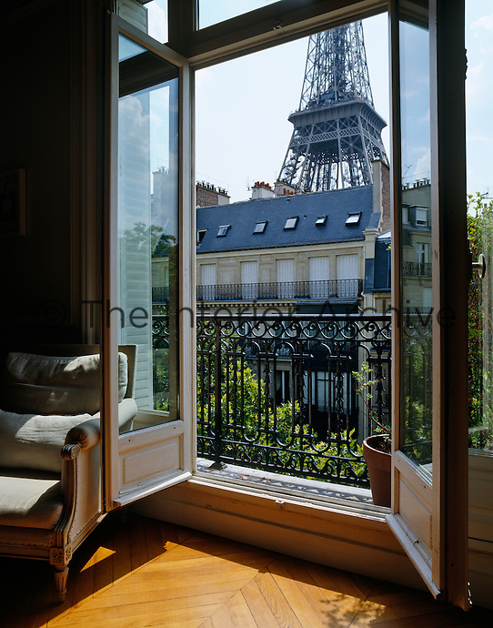 The open windows in this contemporary apartment offer a fantastic view of the Eiffel Tower