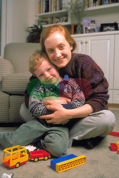 portrait of mother embracing young boy on floor with toys