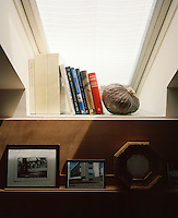 Under a skylight in the living room there is space for a small bookshelf and a plywood ledge displays some framed photographs