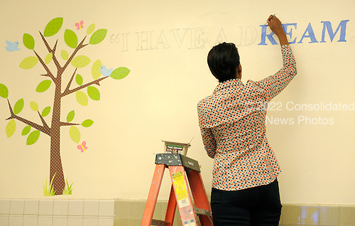 "First lady Michelle Obama paints Martin Luther King Jr's famous phrase "" I have a dream "" as she joins volunteers in a library, participating in a service project, at Browne Education Center, in Washington, DC, USA, on the Martin Luther King Jr national holiday, 16 January 2012. The project was in memory of the legacy of community service, promoted by the late civil rights leader, who was assassinated in 1968.  .Credit: Mike Theiler / Pool via CNP"