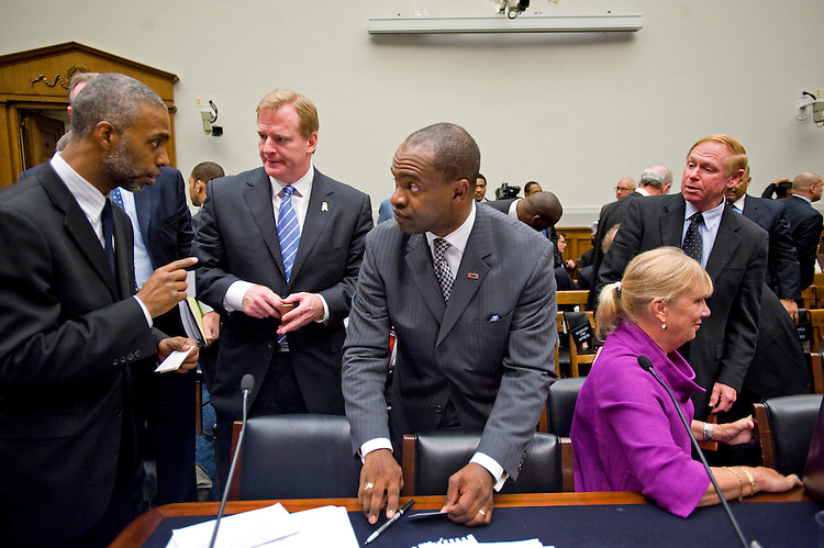 WASHINGTON, DC - Oct. 28: Talib Karim, chief counsel for Rep. Maxine Waters, D-Calif., trades business cards with National Football League (NFL) Commissioner Roger Goodell and DeMaurice Smith, executive director of the NFL Players Association, during a break in the House Judiciary hearing on head injuries among NFL players. At right are Gay Culverhouse, former president of the Tampa Bay Buccaneers; and Robert Cantu, chief of neurosurgery service and director of sports medicine at Emerson Hospital in Concord, Mass. (Photo by Scott J. Ferrell/Congressional Quarterly)