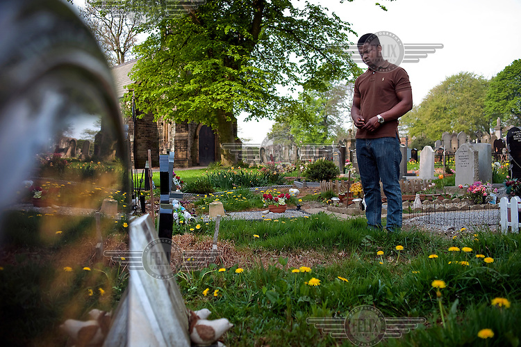 Antonio Bravo stands by the grave of his father Manuel, who committed suicide in order to stop his son being deported back to Angola. Leeds.