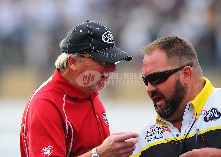 Aug. 5, 2011; Kent, WA, USA; NHRA team owner Alan Johnson (left) talks with NHRA official Jeff Parker during qualifying for the Northwest Nationals at Pacific Raceways. Mandatory Credit: Mark J. Rebilas-