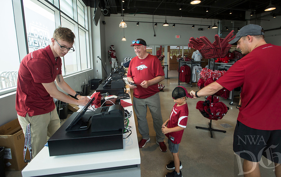 NWA Democrat-Gazette/BEN GOFF @NWABENGOFF             Austin Greek (from left), rings up a purchase for Brad Thomas, a former Arkansas defensive back, and his grandson Brady Thomas, 5, and son Austin Thomas of Van Buren Wednesday, Aug. 7, 2019, at the new Hog Heaven shop on the North side of Reynolds Razorback Stadium in Fayetteville.