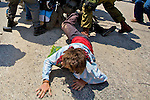 An international activist crawls away from a scuffle after being knocked to the ground during a non-violent demonstration in the West Bank village of An Nabi Salih near Ramallah on 09/07/2010.