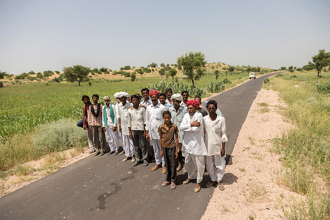 04 September, 2013, Jodhpur, Rajasthan INDIA : Village elders walk the new road at Boongari Village, District Jodphur and speaking about  how the Pradhan Mantri Gram Sadak Yojana program (PMGSY) has made a difference to their lives in Rajasthan. The roads have allowed them to move in medical supplies and increased the village income by more efficiently getting crops to market. It also means the women don't have to hand mill the grain but can transport it to a local mill. PMGSY is a nationwide plan in India to provide good all-weather road connectivity to unconnected villages.<br /> It is under the authority of the Ministry of Rural Development and was begun on 25 December 2000 It is fully funded by the central government and implemented in conjunction with the World Bank<br /> The goal was to provide roads to all villages  with a population of 500 persons and above by 2007, in hill states, tribal and desert area villages with a population of 250 persons and above by 2007. Picture by Graham Crouch/World Bank