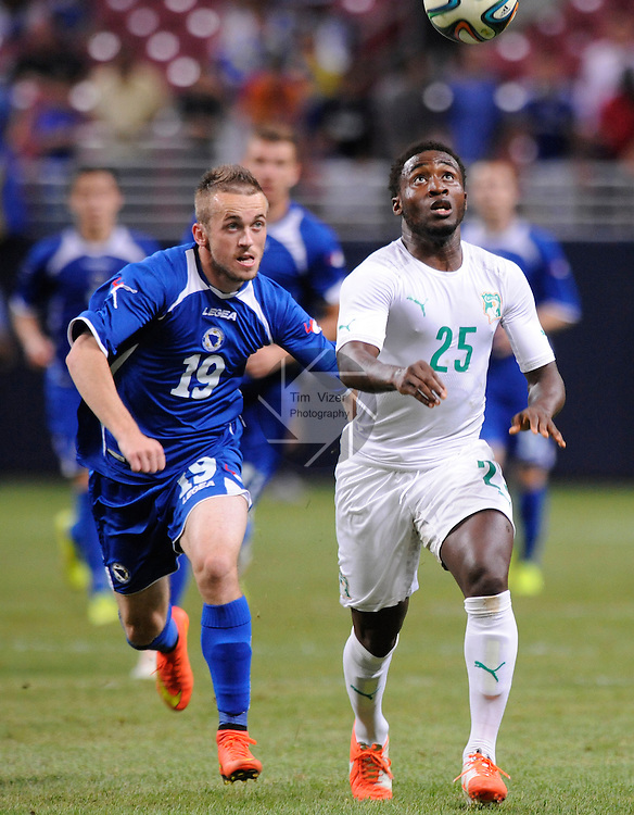 Soccer - International Friendly - Bosnia- Ivory Coast.<br /> Bosnia's Edin Visca (19,left) runs with Ivory Coast's Brice Dja Djedje (25) as they keep focused on the ball in the second half. Bosnia played Ivory Coast in an international friendly game during &quot;The Road To Brazil&quot; series. The game was played at the Edward Jones Dome in St. Louis, Missouri on Friday May 30, 2014.