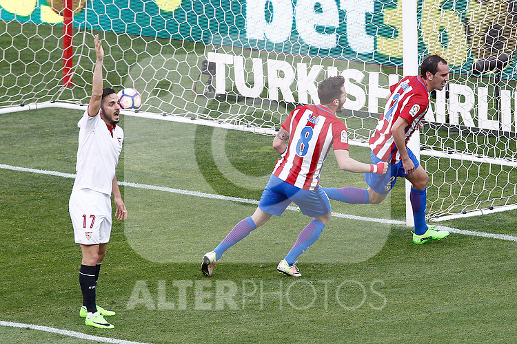 Atletico de Madrid's Diego Godin (r) and Saul Niguez (c) celebrate goal in presence of Sevilla FC's Pablo Sarabia during La Liga match. March 19,2017. (ALTERPHOTOS/Acero)