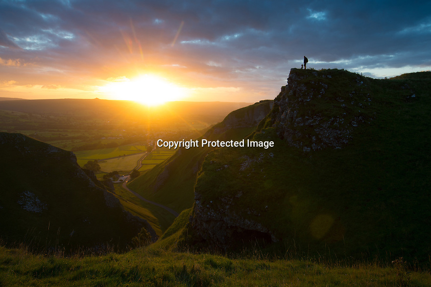 25/08/15<br /> <br /> A man stops with his dog to admire a late summer dawn breaking over Winnats Pass near Castleton in the Derbyshire Peak District.<br />  <br /> All Rights Reserved: F Stop Press Ltd. +44(0)1335 418629   www.fstoppress.com.