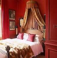 A fragment of Aubusson is used as the bed hangings in this bedroom with red painted walls