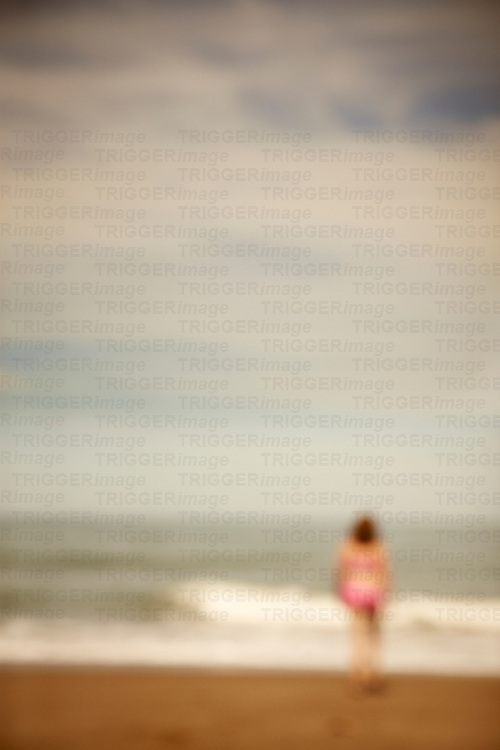 A woman standing on a deserted beach at the seas edge with waves