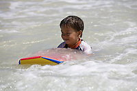 A small boy bodyboards at Kailua Beach, Oahu, Hawaii.